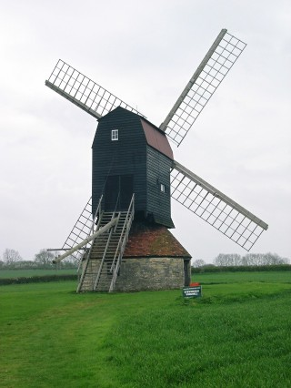 windmill with four sails in the middle of a green field; wooden steps leading to a door halfway up the buiding | photo: Nicola Avery